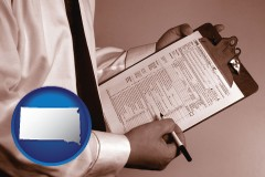 south-dakota map icon and a tax consultant holding an IRS form 1040