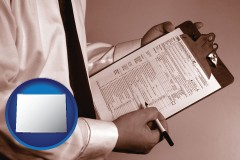 wyoming map icon and a tax consultant holding an IRS form 1040